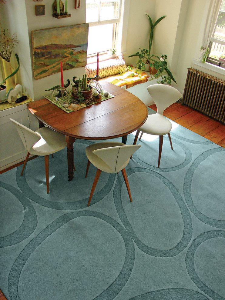modern dining room drop leaft wooden table modern white chairs with angled wood legs blue rug with modern patterns