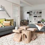 modern living room a cluster of table stool made of wooden textured white rug grey couches metallic finish floor lamp