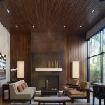 Modern Living Room Design Wood Siding Walls And Ceilings Darkwood Covered Fireplace Modern Lantern Wall Lamps Concrete Wall Panel Light Beige Couch Earthy Brown Throw Pillows Wood Reclaimed Floors