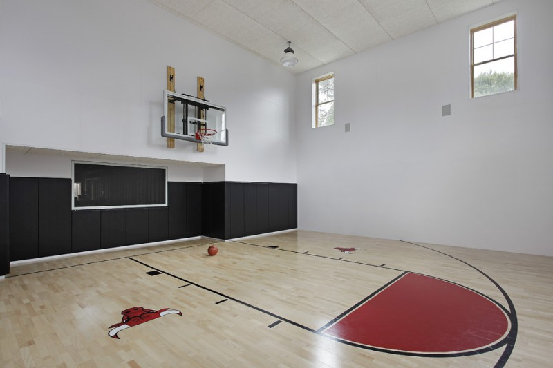 modern minimalist indoor basketball court design light wood floors with red accent white painted walls with black accent two decorative windows
