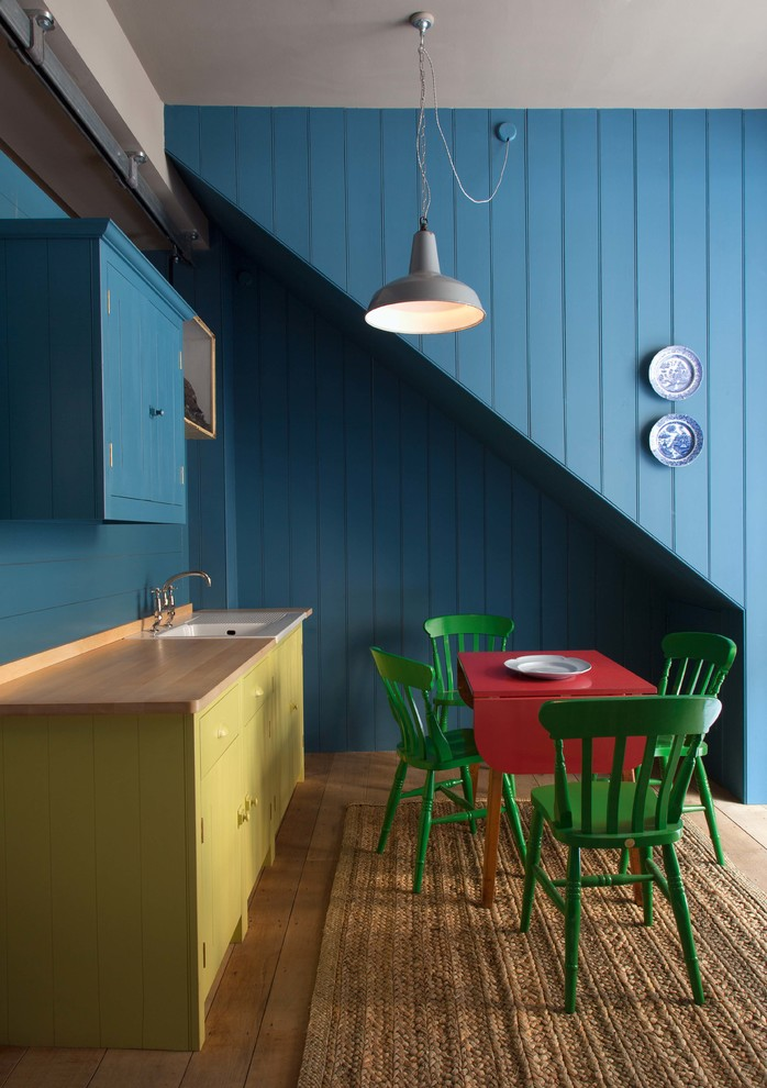 retro style breakfast nook red drop leaf table green chairs yellow counter with light wood top white ceramic undermount sink blue top cabinets blue wood siding walls traditional pendant
