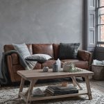 scandinavian style living room distressed brown leather sectional light wood coffee table concrete walls