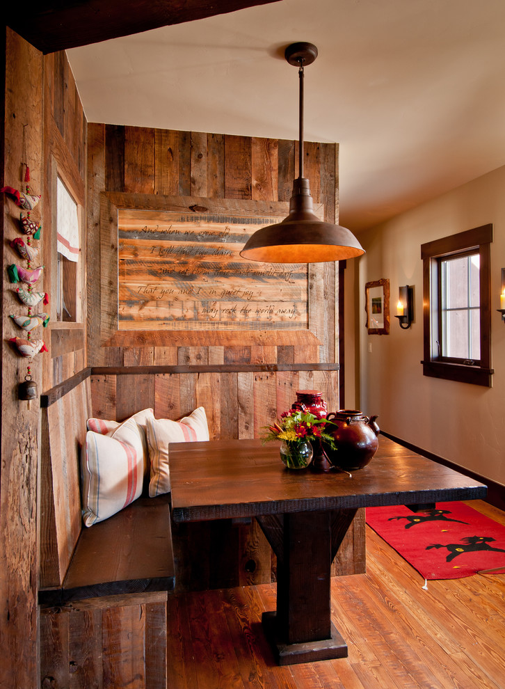 small rustic breakfast nook for ranch cabin built in wooden banquette white throw pillows dark wood table dark wood floors wooden walls