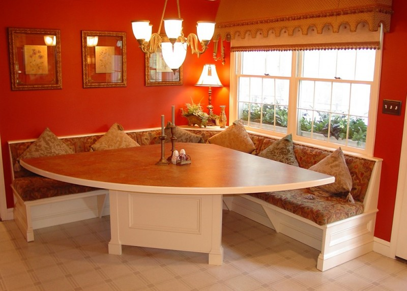 traditional dining room wider triangle dining table with white base larger L shaped built in bench seat traditional chandelier red painted walls white tiled floors