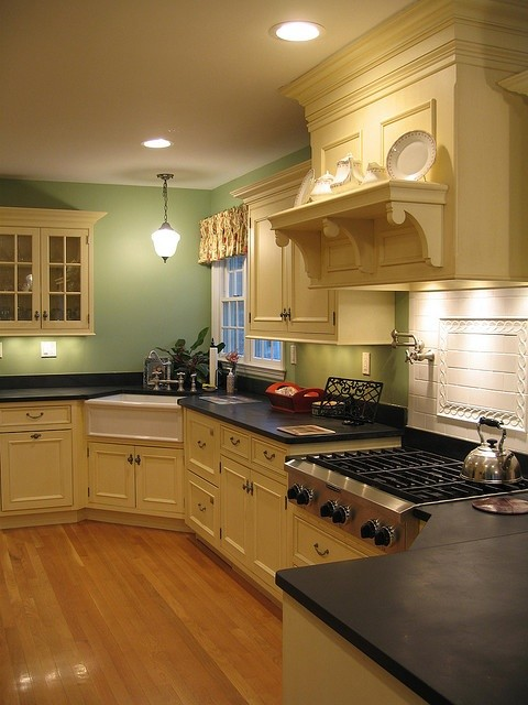 traditional kitchen recessed farmhouse corner sink in white solid black countertop cream painted cabinets with classic handles green painted walls medium toned wood floors