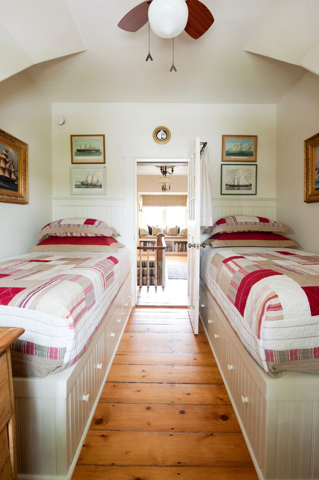 traditional twin beds with deep drawers medium toned wood boards floors white painted walls with framed wall decors