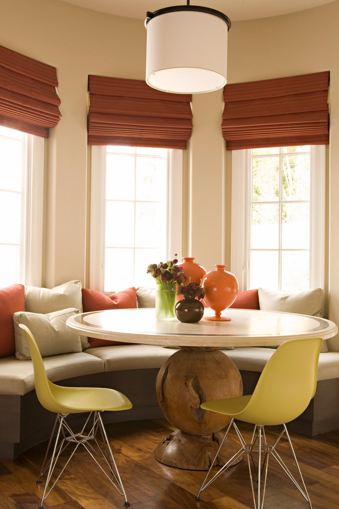 transitional breakfast corner curved bay windows corner built in bench seat white round top table yellow scandinavian chairs dark wood floors white and orange throw pillows