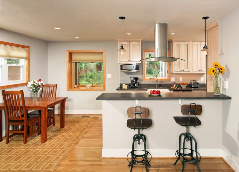 transitional kitchen design industrial bar stools with back feature dark countertop stainless steel appliances light wood floors light wood colored rug with motifs reddish wooden chairs and table