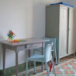 vintage tiled floors grey working table blue chairs grey wardrobe white painted walls