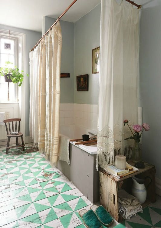 Bohemian bathroom light toned shower curtains modern tub with white subway tiled wall graphic patterned tiles flooring small wooden chair hanging plant