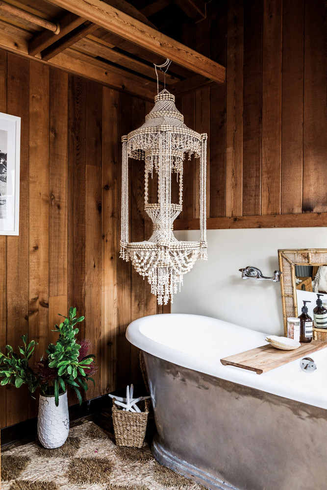 Bohemian bathroom with wood element wood plank wall wood ceiling beams handmade pendant in white white bathtub light shag rug