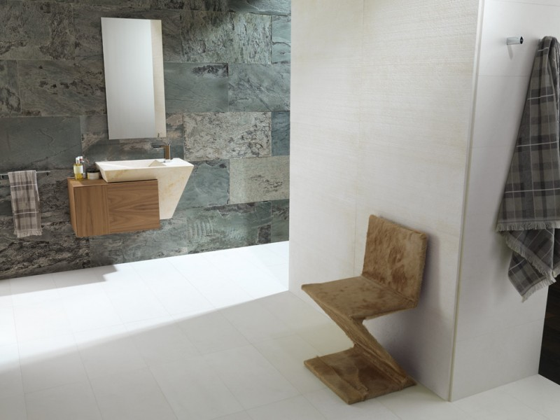 Contemporary stone bathroom idea rough textured stone walls contemporary floating sink and single wood cabinet contemporary wood chair frameless mirror