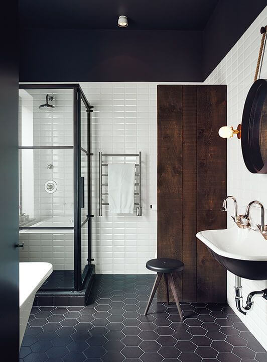 Scandinavian bathroom with darker shades white ceramic tiled wall hexagon tiled floors in black walk in shower with clear glass panel and black frame black wall mounted sink dark wood closet