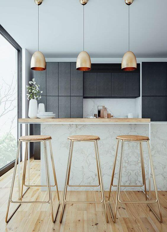 Scandinavian home bar idea wood round top bar stools with gold toned legs wood top bar table black flat paneled cabinets modern pendant with gold tone lampshade light wood floors