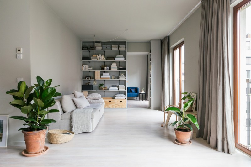 Scandinavian open concept living room in light gray simple shelf with under wood cabinets contemporary sofa in white white throw pillows white blanket clay burnt planters some interior plants