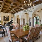Tuscan open concept dining room with higher ceilings larger wooden dining table large party dining chairs with flower motifs great chandelier a music corner