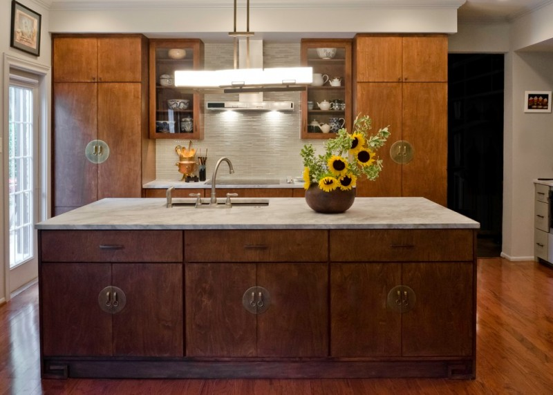 asian inspired kitchen wooden cabinets with Asian pulls marble countertop textural white backsplash upper display cabinets with glass doors