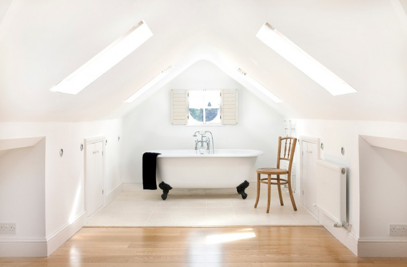 clean look and bright bathroom in attic claw foot bathtub in white white ceramic floor light wood floors skylights center window light wood chair