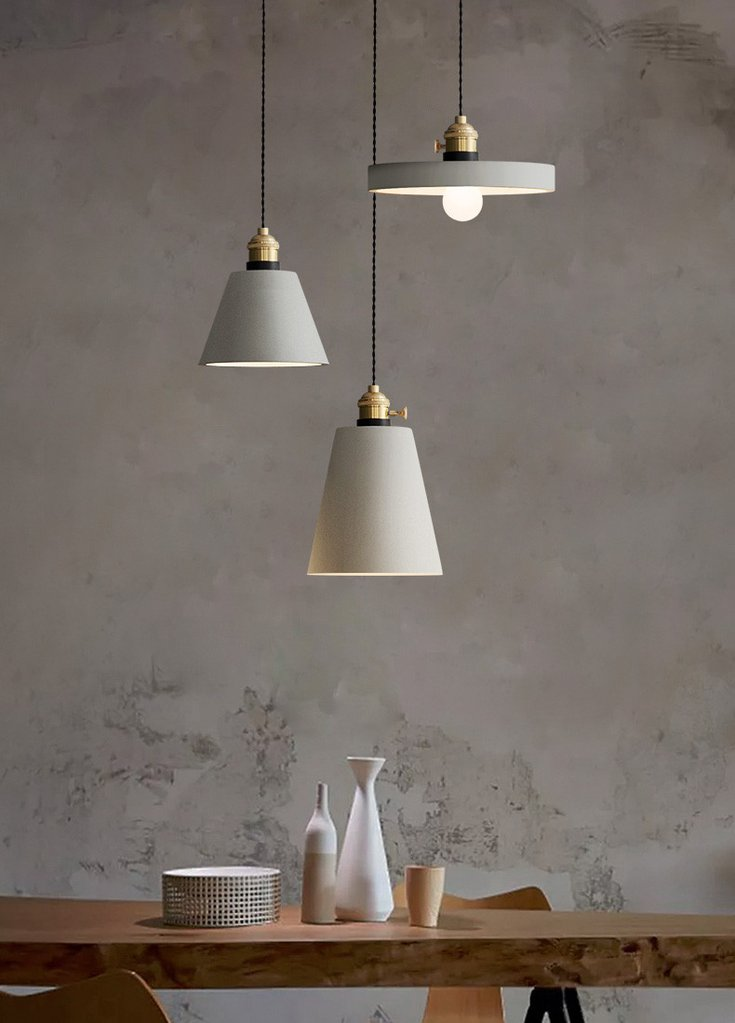 concrete Vasa Pendants in minimalist light gray concrete walls light wood table and chairs