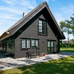 Contemporary Exterior With Scandinavian Appeal Dark Wood Siding Exterior Walls Glass Windows Glass Door Black Wrought Iron Outdoor Bench With Back Rest