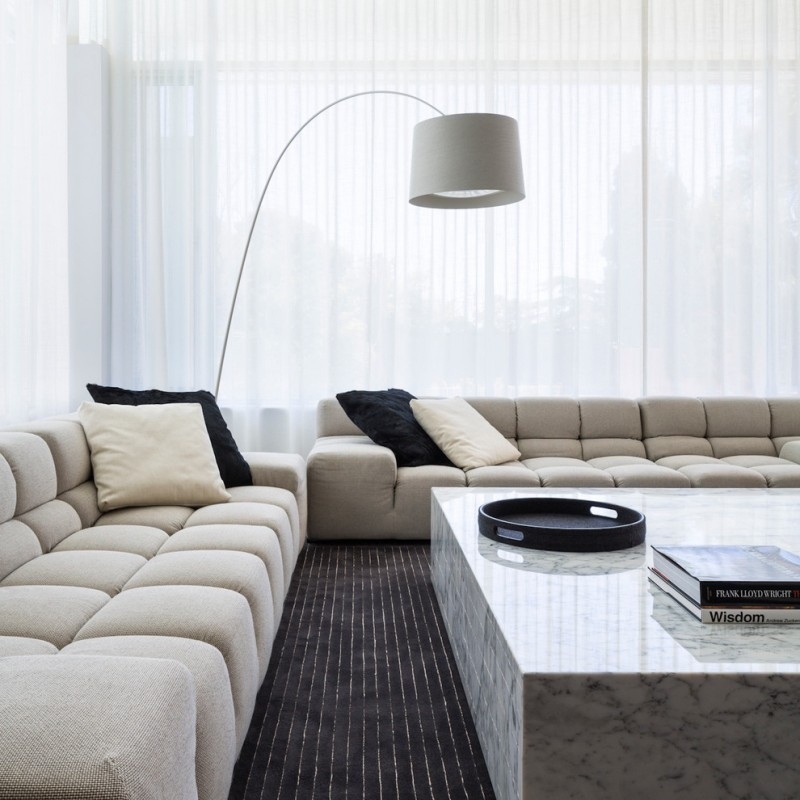 contemporary living room idea light tanned couches tanned throw pillows black throw pillows black area rug with accent lines clean lined marble coffee table modern floor lamp with white lampshade