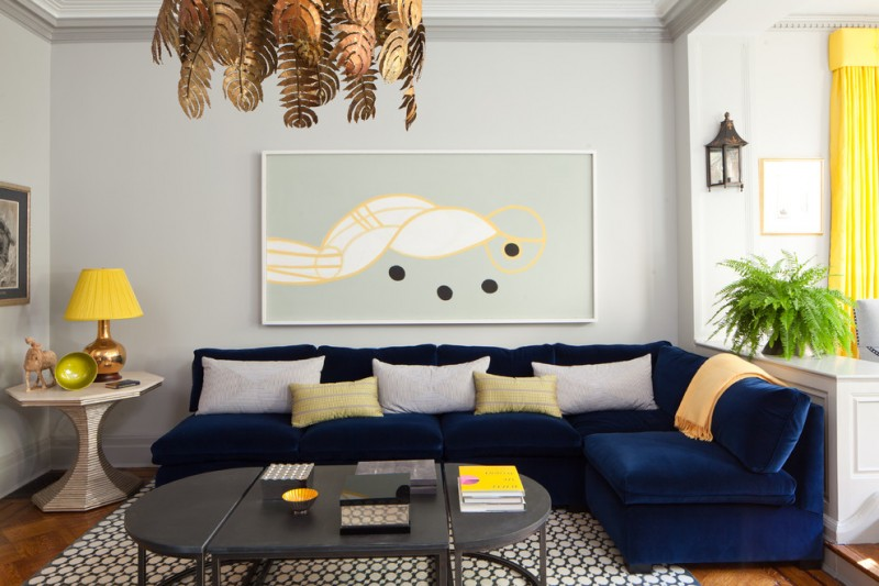 contemporary living room idea navy blue velvet sofa yellow and white throw pillows folding coffee table trendy area rug ceramic side table abstract print