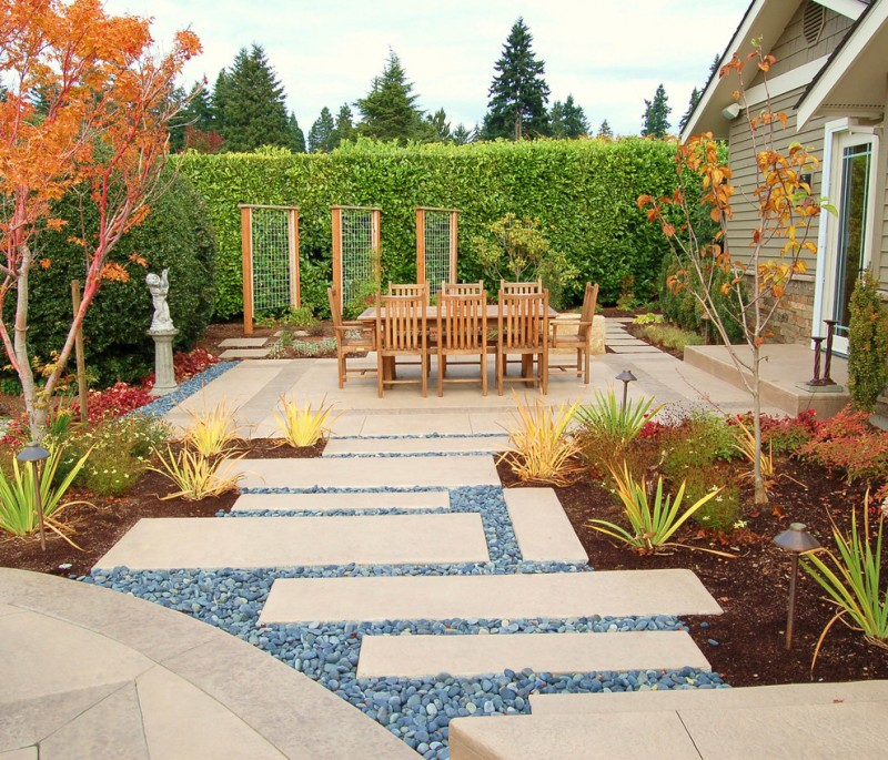 contemporary patio with rectangular concrete stepstone pavings light wood furnishings vertical garden