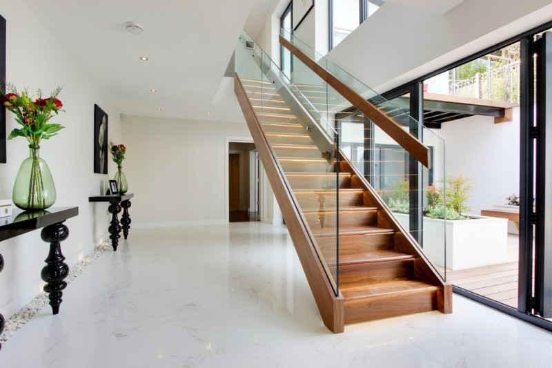 contemporary staircase with wooden handrails inside the glass panels