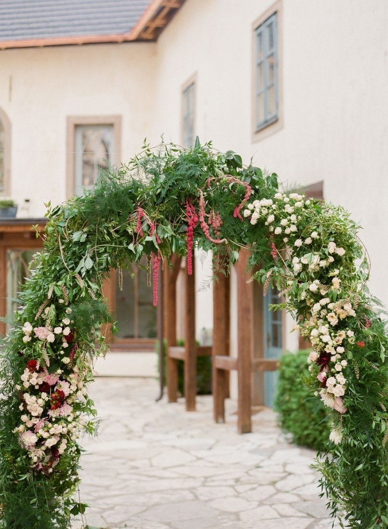 curved green garland idea accented by small blosomming flowers