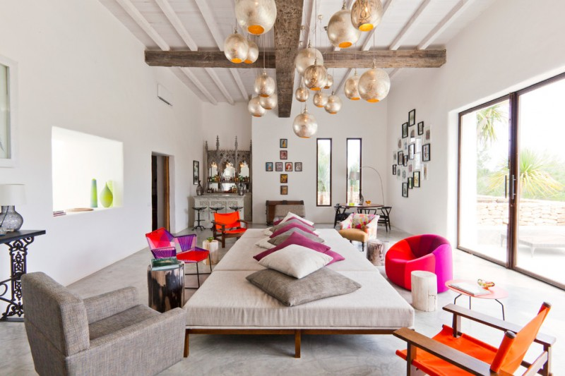 eclectic living room colorful seats giant gray table with pile of throw pillows silver finishing pendants in vintage style clean look walls in white exposed wood beams white ceilings