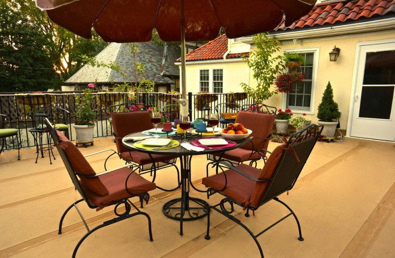 eclectic rooftop idea black wrought iron furniture maroon outdoor umbrella black wrought iron railings light brown floors