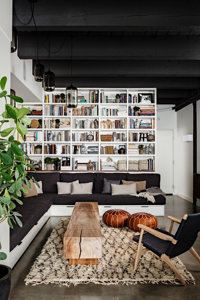 industrial living room design full height bookcase in white L shaped modern couch with under storage butcher block coffee table black chair with wood construction