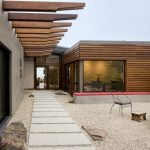 Midcentury Modern Exterior Idea Concrete Stepstones In Rectangular Shape Wood Siding Exterior Wall Wood Arbors Secured By Ceilings
