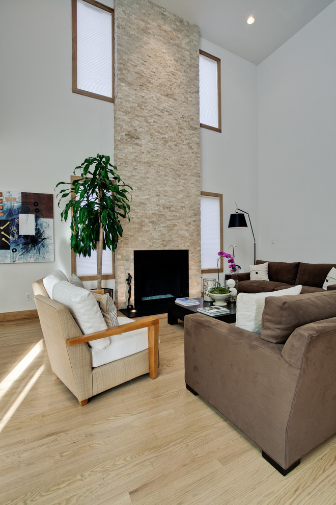 modern high ceiling living room white & clean lined ceilings white wall color with accent windows standard fireplace with stone surrounding modern mocca sofas light brown chair light wood floors