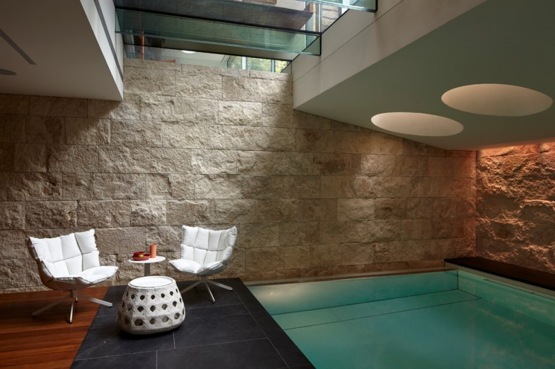 modern indoor swimming pool hard textured stone walls black tiled floors dark wood floors large skylights
