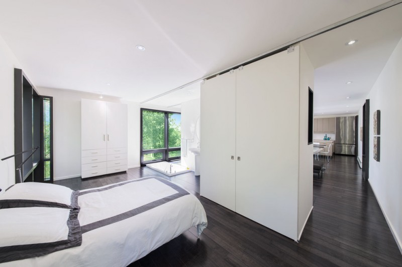 modern minimalist bedroom in open concept white cabinets white bedding with black square accent black wood floors white ceilings