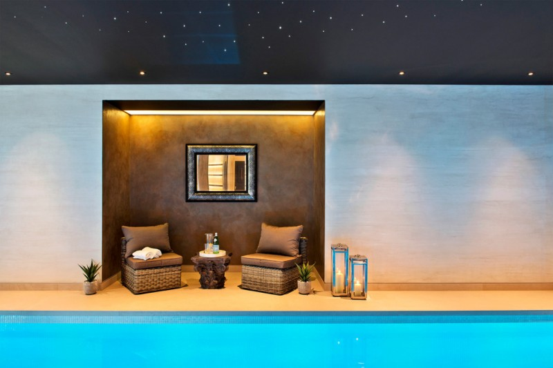 modern minimalist indoor swimming pool little seating nook with dark background and warm light effect a pair of armrest less chairs centered decorative wall mirror