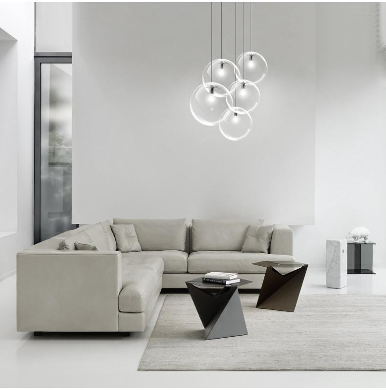 modern minimalist pendants with clear glass lampshade light gray sofa with throw pillows modern black coffee tables light gray area rug