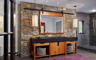 modern rustic bathroom design stone wall wood bathroom vanity with black countertop wood framed mirror purple rug gray tiled floors