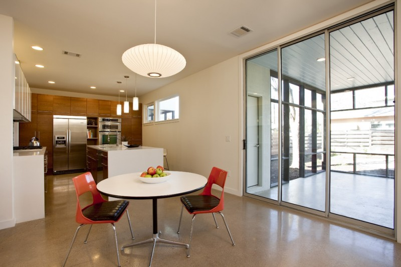 open concept dining space giant pendant with white lampshade white round top dining table modern red dining chairs