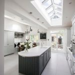 open concept kitchen with high angled glass ceilings white laminated top kitchen island white tiled floors modern pendants