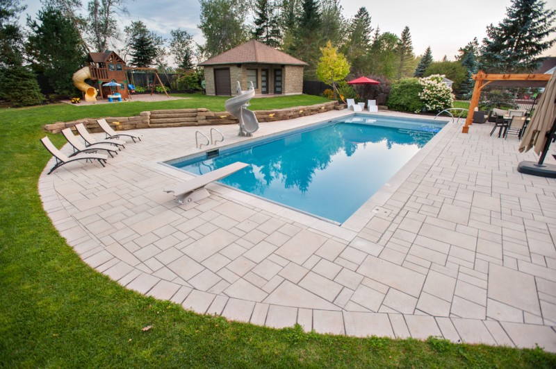 resort like pool house with concrete hardscaping modern outdoor furnishings natural stone walls