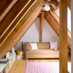 Scandinavian Attic Reading Nook With Exposed Wood Beams Mocca Toned Sofa White Throw Pillows Light Wood Plank Floors White Floor Shelves