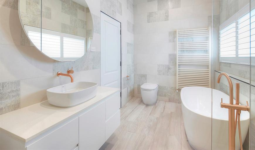 scandinavian bathroom white floating bathroom vanity with flat paneled cabinets white sink round mirror without frame very light wood floors white bathtub clear glass panel