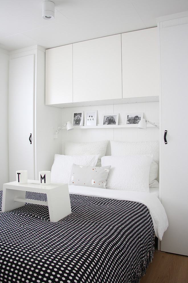 scandinavian bedroom in white monochromatic bedding white pillows flat paneled cabinets in white light wood floors