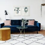 Scandinavian Living Room Dark Blue Velvet Sofa In Modern Style Round Top Coffee Table With Thin Metal Legs Caramel Ottoman Modern White Rug With Black Accents Modern Side Tables Light Wood Floors