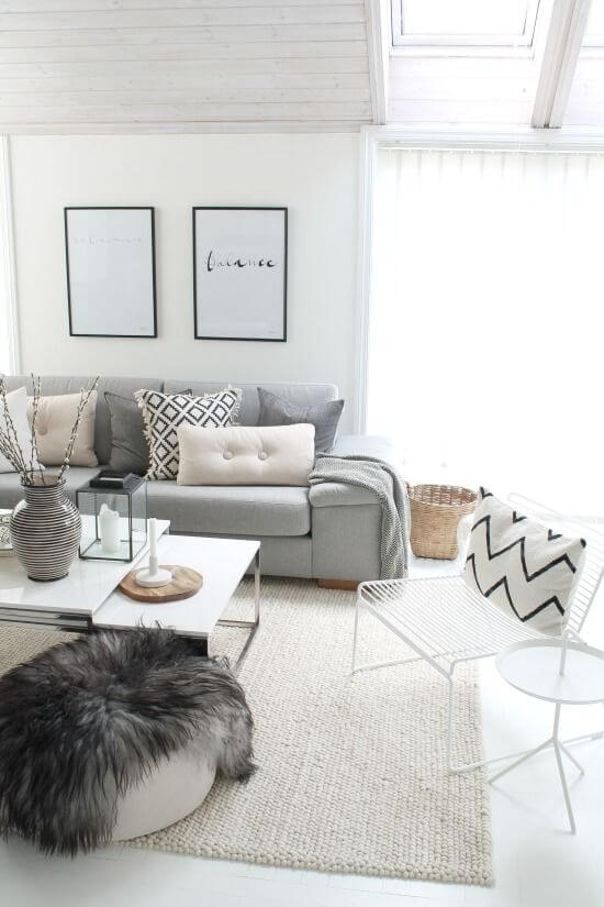 scandinavian living room design light gray couch white top coffee table white pouf with black fury blanket white knitted rug