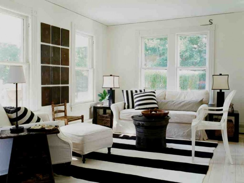 shabby chic living room idea striped black and white area rug striped black and white throw pillows white sofa slipcover white ottoman white chair black finish side table