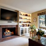 Tan Living Room With Classic Appeal Yellow Lighted Recessed Shelves Standard Fireplace With Red Brics Surround Soft Beige Couch Cream Painted Walls Woven Rattan Coffee Table With Glass Top