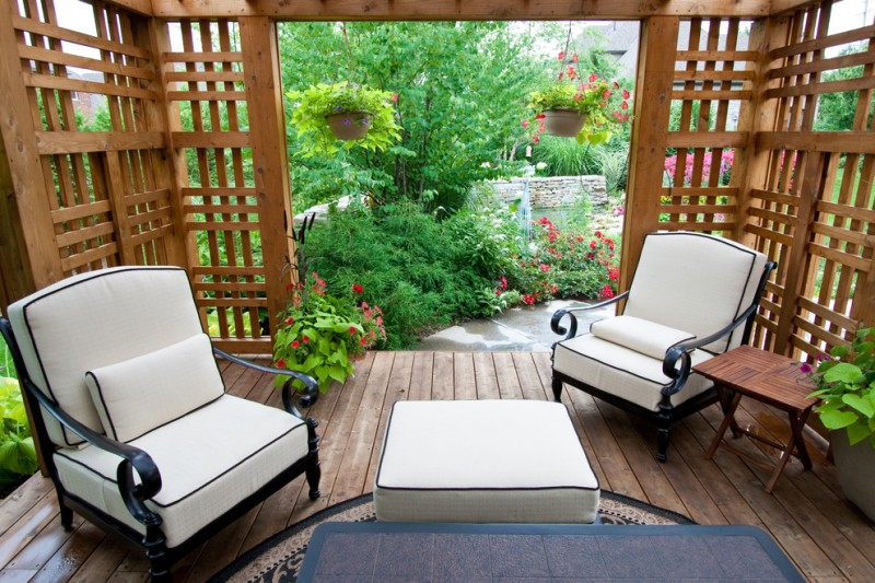 traditional patio idea wood decking floors wood enclosure and partitions black wrought iron chairs with classic curly armrests ottoman table